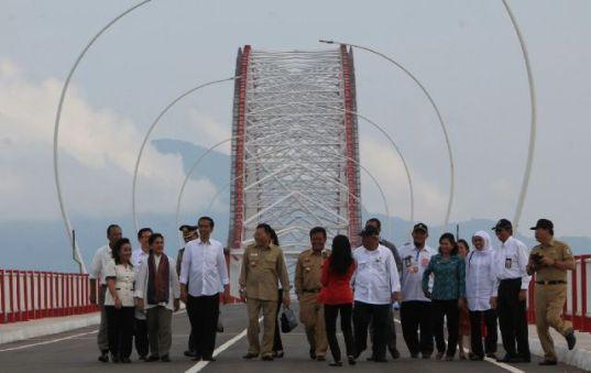Presiden Jokowi bersama sejumlah menteri dan pejabat negara berjalan kaki usai meresmikan Jembatan Pak Kasih Tayan, di Kalbar.