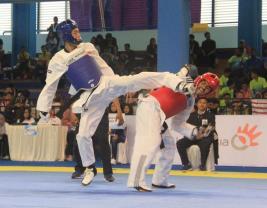 Atlet Taekwondo Kaltara Chaerul Adzan (biru) berhasil melancarkan tendangan ke kepala atlet NTT Rocky di babak final Kelas Gyorugi Under 63 kilogram di Gymnasium FPOK UPI Kota Bandung, Minggu sore (25/09).