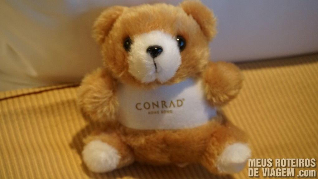 Ursinho de pelúcia da rede Conrad em cima da cama