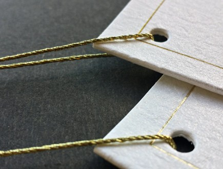Tags of thick cream-colored stock with a gold metallic border strung with 4-ply gold lamé.