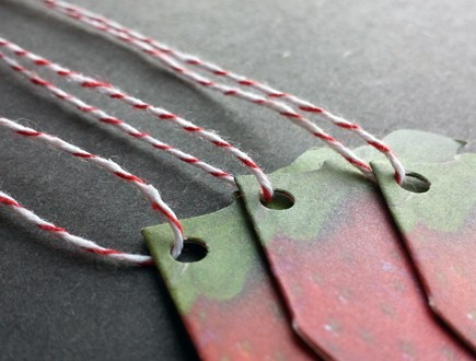 Folded die-cut strawberry-shaped tags strung with red bakery twine.