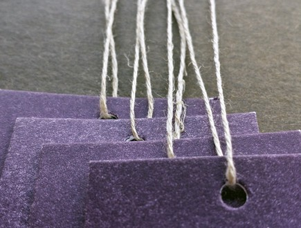 Tags on purple stock strung with our 3-ply hemp.