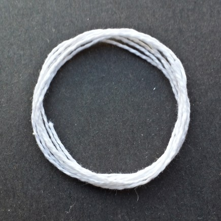 Photograph of a coil of lightweight 5/2 mercerized cotton in white.