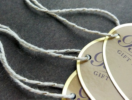 Foil-stamped oval tags strung with our gold-natural metallic yarn.