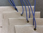 Brown paper envelopes strung with blue non-fray elastic.