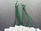 White tags with gold copy strung with green non-fray elastic.