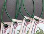 Stitched booklets strung with green non-fray elastic.