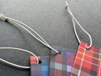 Plaid tags strung with white non-fray elastic.