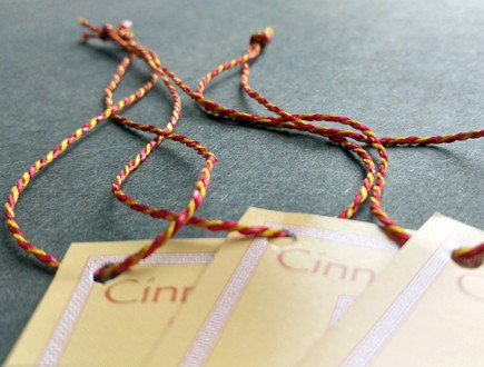 Tags with a printed border strung with custom red/yellow 2400 Pearlray.