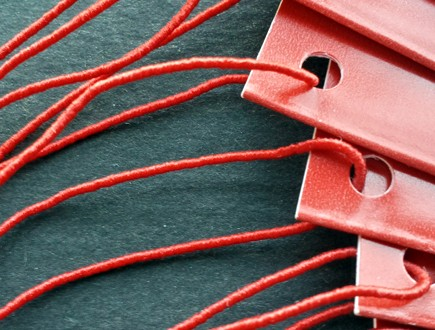 Folded red tags strung with standard elastic in red.