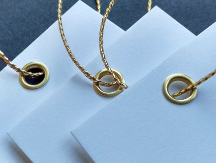Tags of heavy white stock reinforced with our brass eyelets and strung with our gold tinsel cord.