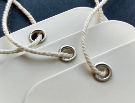 Round-cornered tags of glossy white cover stock reinforced with our nickel eyelets and strung with our cotton rope cord.