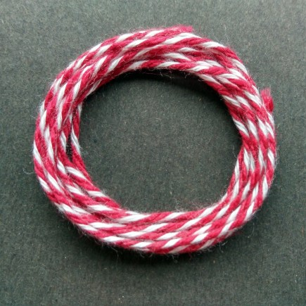 Coil of heavyweight variegated red-white cotton string.