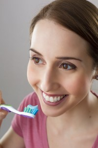smiling woman holding tooth brush