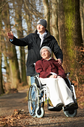 Elderly woman in wheelchair walking with son