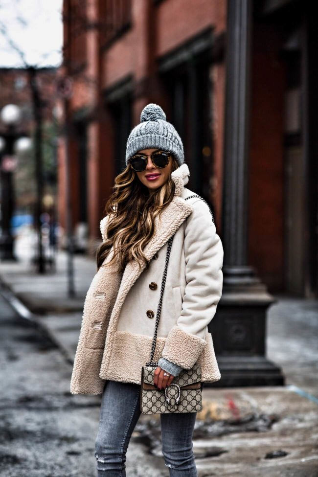 fashion blogger mia mia mine wearing a gray beanie and gucci dionysus bag and mother jacket from bloomingdale's