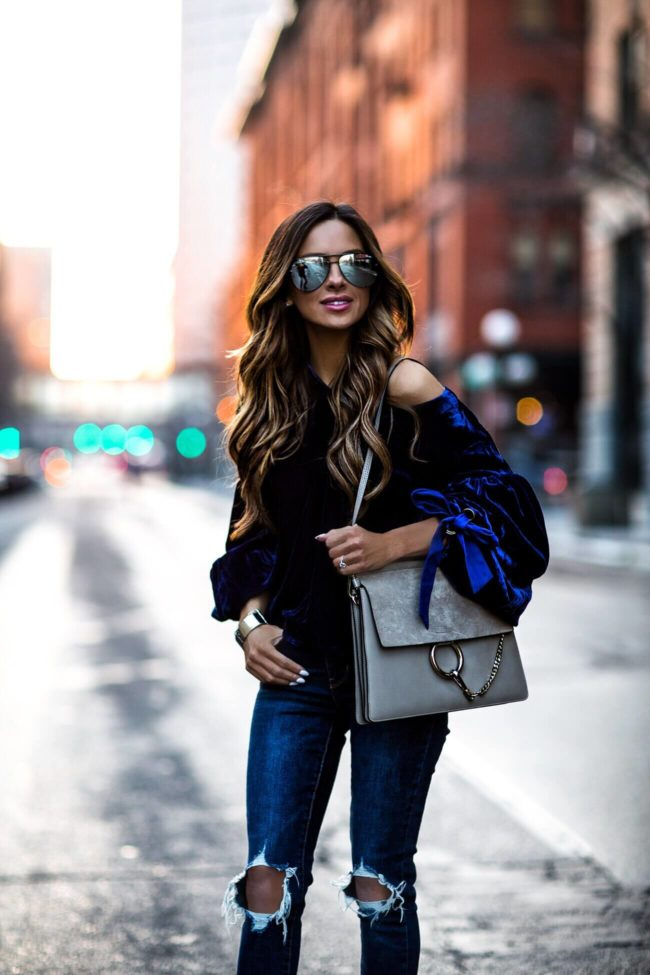 fashion blogger mia mia mine wearing a blue velvet free people top and quay sunglasses