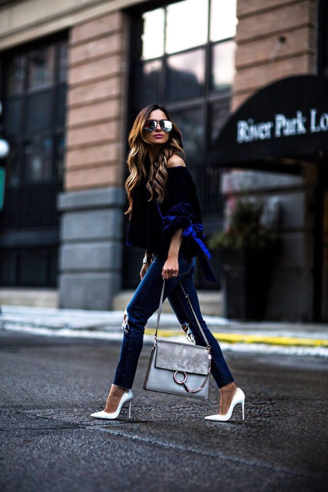 fashion blogger mia mia mine wearing a sapphire blue velvet top and white louboutin heels