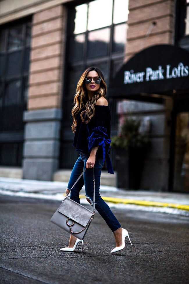 fashion blogger mia mia mine wearing a blue velvet top and levi's denim