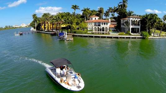 A white motorboat sailing past a luxurious home on the beach, MiamiCurated