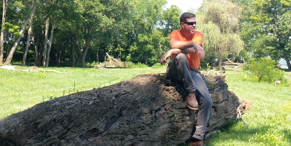 Michael Colemire sits atop a log that is about to become live-edge slabs.