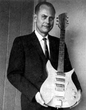 George Beauchamp holding a Rickenbacker guitar.