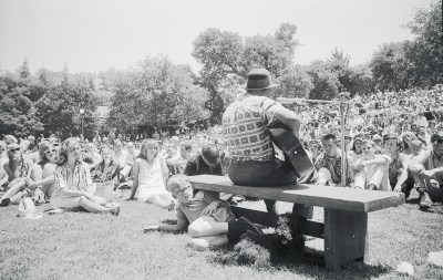 Mississippi John Hurt performing in the Faculty Glade, 1964 Berkeley Folk Music Festival, University of California (with child and dog below him). Photographer unknown.