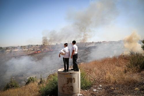 Ultra orthodox watch fire fighters trying to extinguish a forest fire which broke out in the area of Ramat bet Shemesh, outside of Jerusalem on September 20, 2016. Photo by Yaakov Lederman/Flash90 *** Local Caption *** ùøéôä øîú áéú ùîù çøãéí çøãé éìãéí