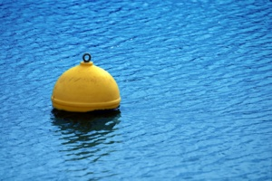 Yellow buoy on blue sea surface