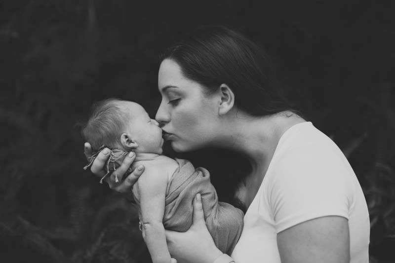 Woman in White Shirt Kissing Her Baby