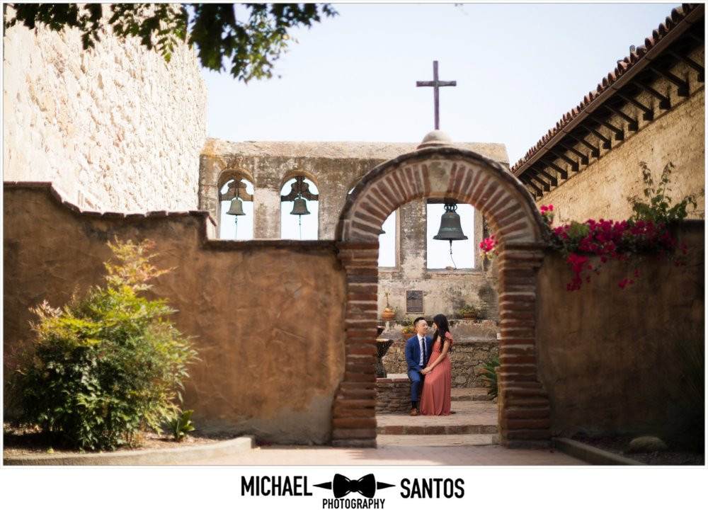 couple sitting by the fountain during their mission san juan capistrano engagement session