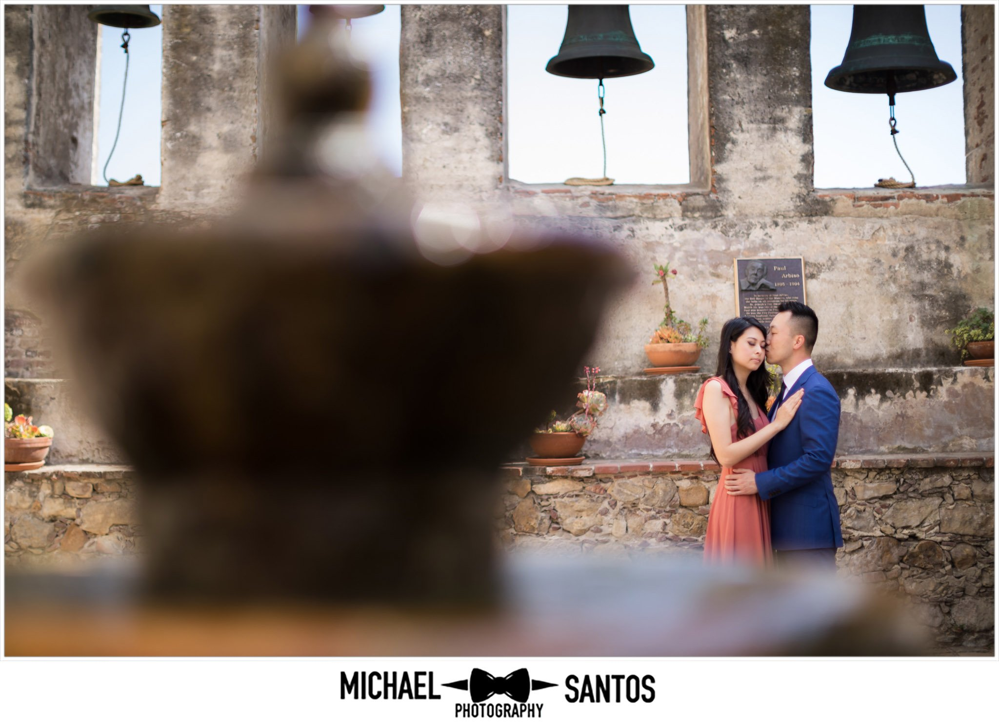 couple kissing under the bells at their mission san juan capistrano engagement session