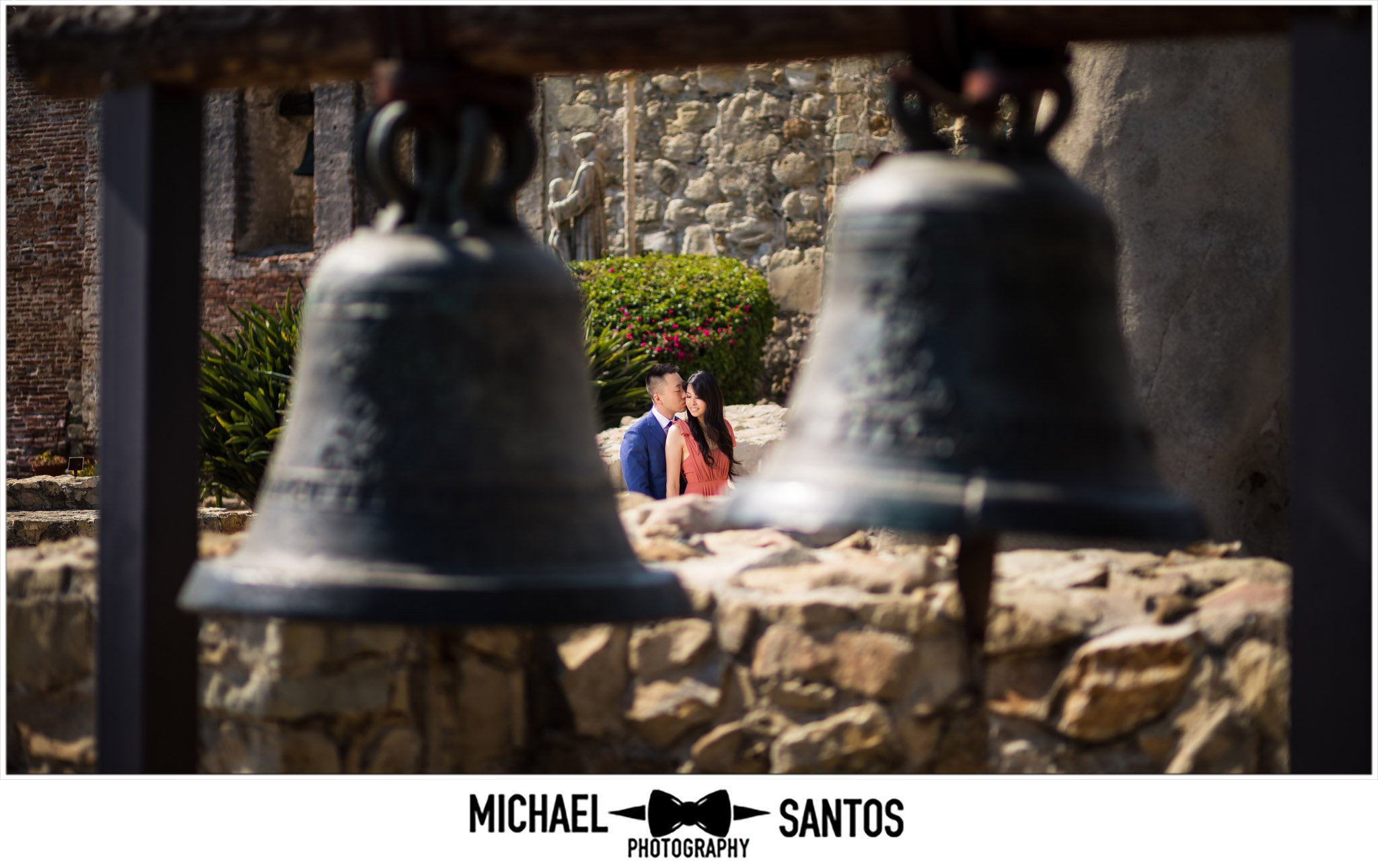 couple standing in between bells at their mission san juan capistrano engagement session