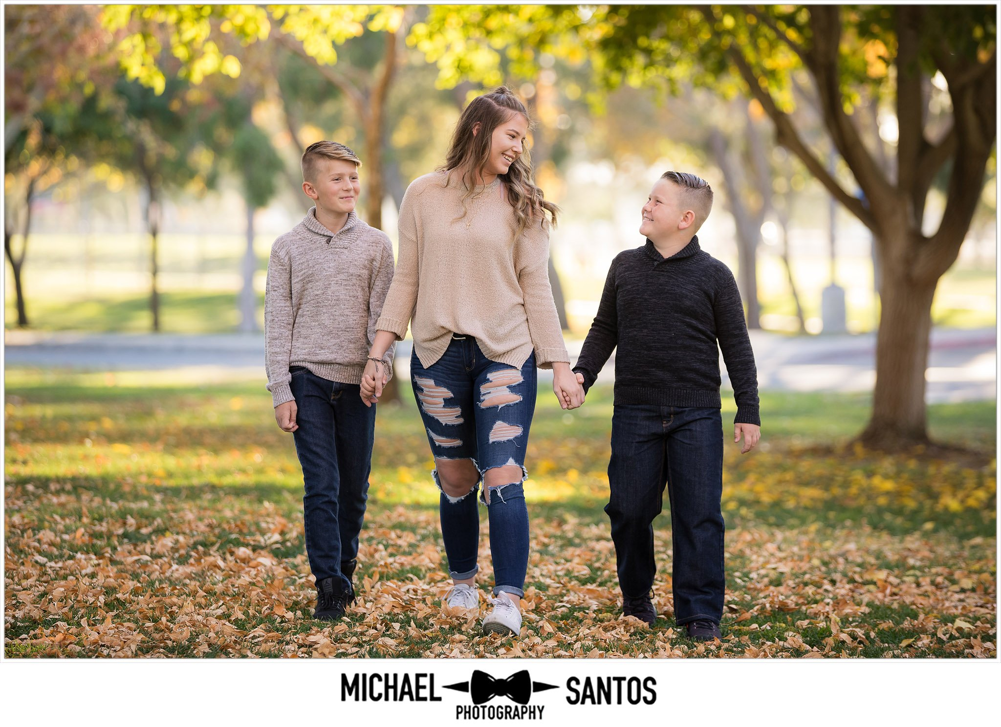 three siblings walking during their family portrait session in lancaster california