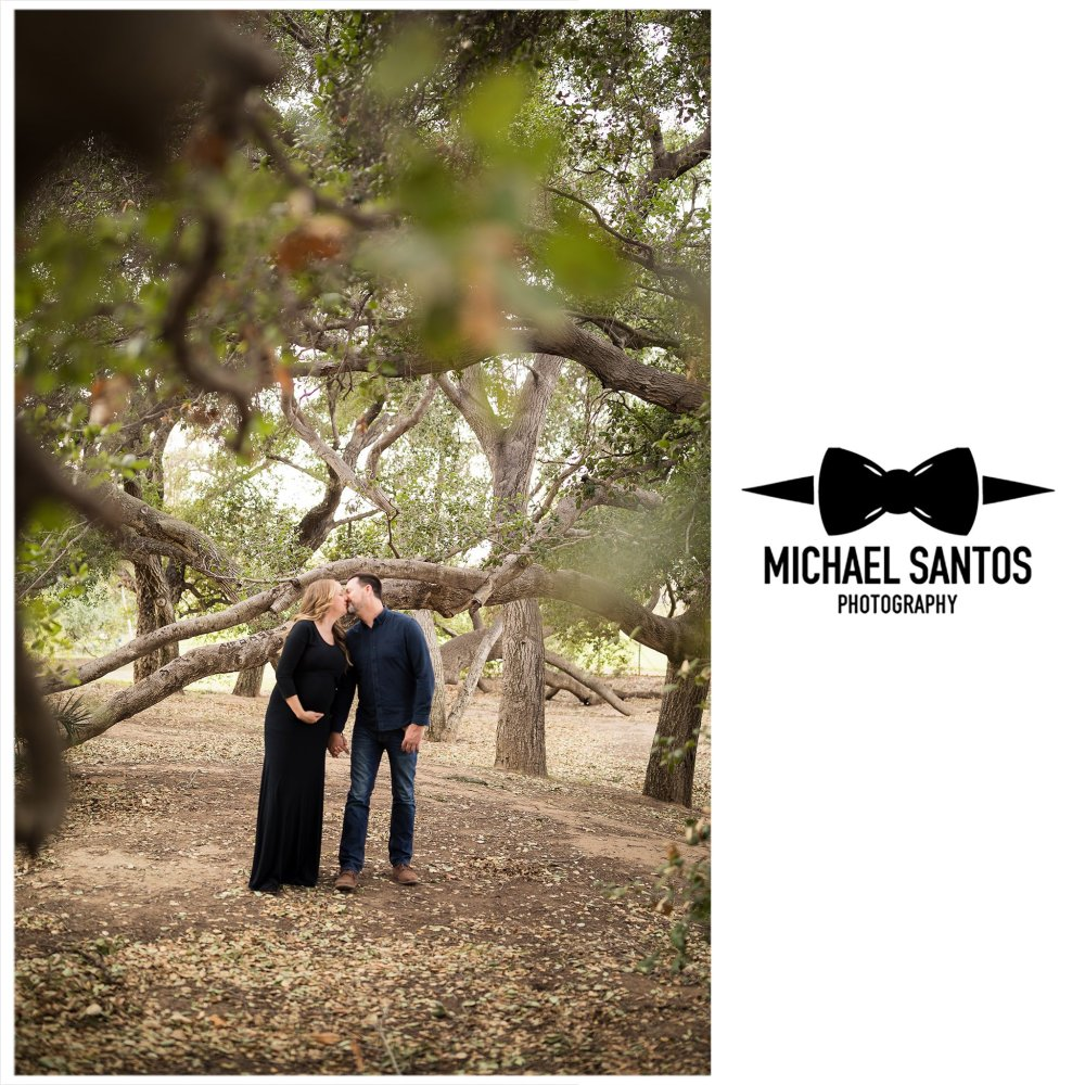 husband and pregnant wife leaning and kissing each other at irvine regional park maternity session