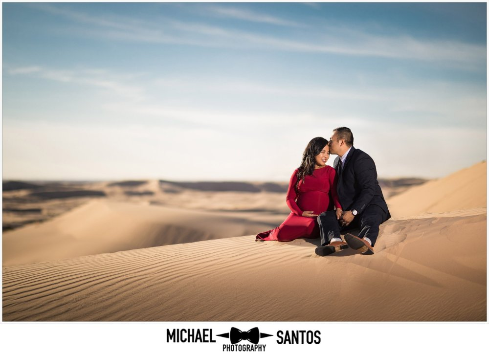 epic portrait of couple sitting in the sand dunes for their glamis maternity session