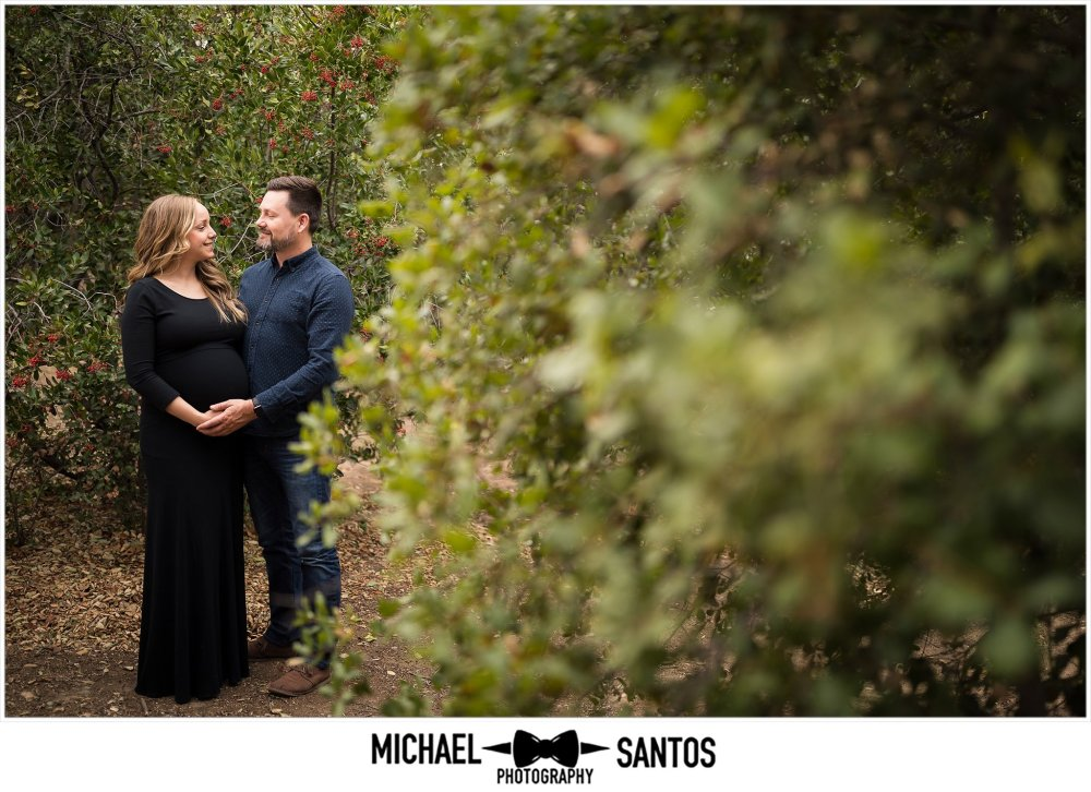 expecting wife and husband holding belly looking into each others eyes at irvine regional park