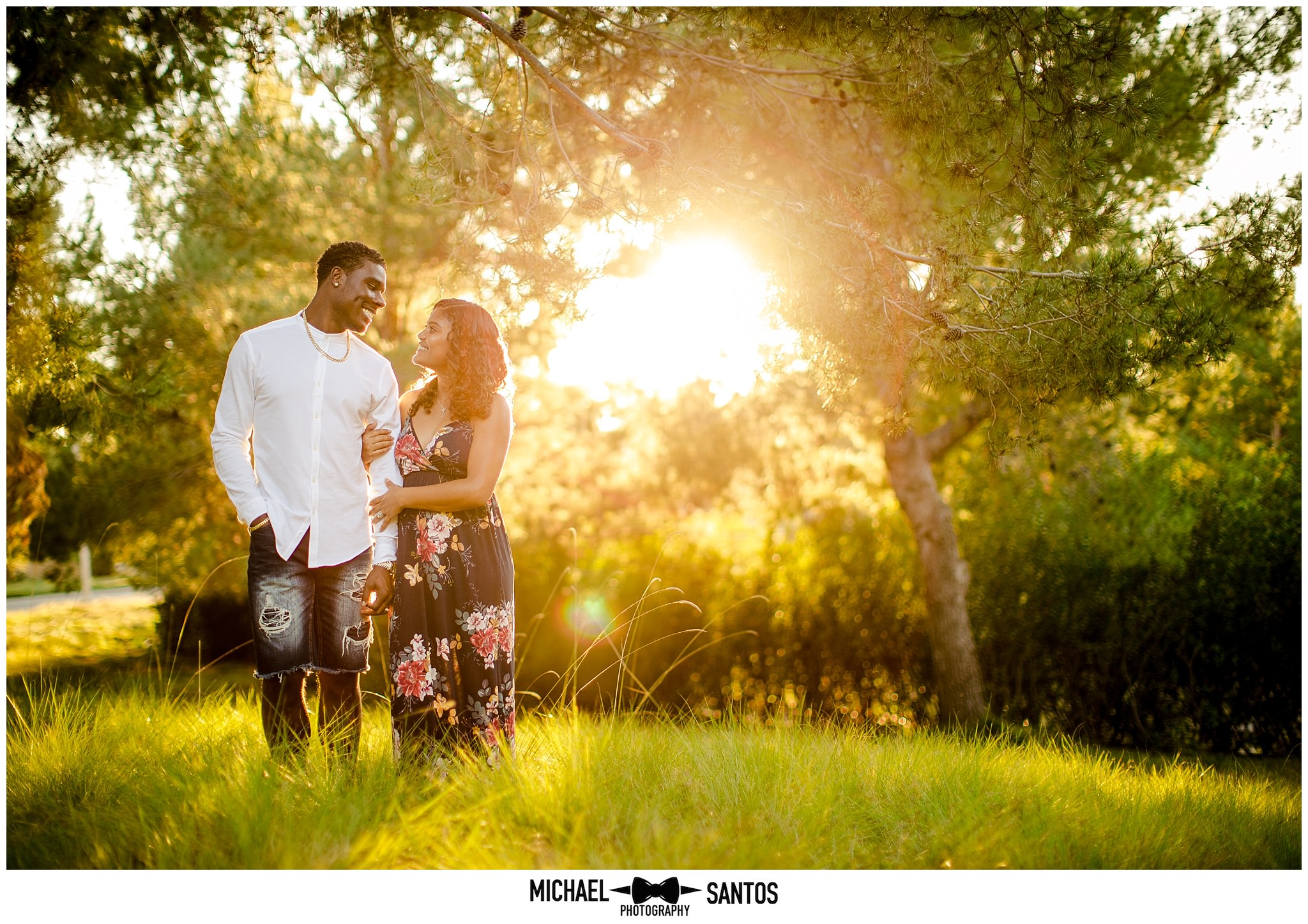 couple standing in a field with the sun setting behind them during their baby announcement photos