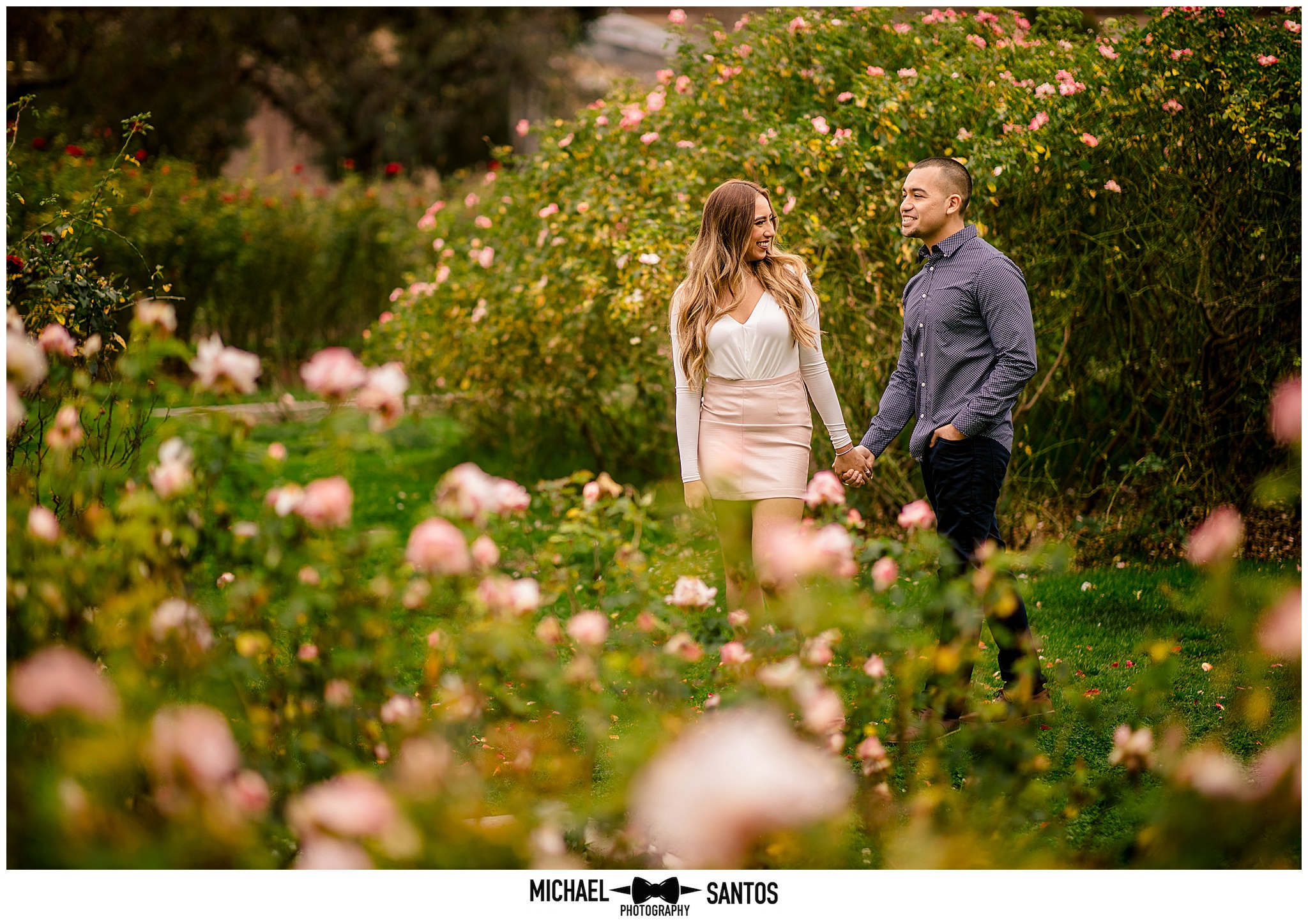couple walking through the rose garden at usc during their engagement photography session