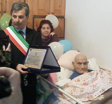 Sindaco Carmelo Panetta consegna una targa ricordo al festeggiato.