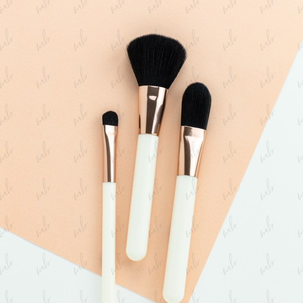 Beauty styled stock photo - makeup brushes flatlay on a white and peach geometric background
