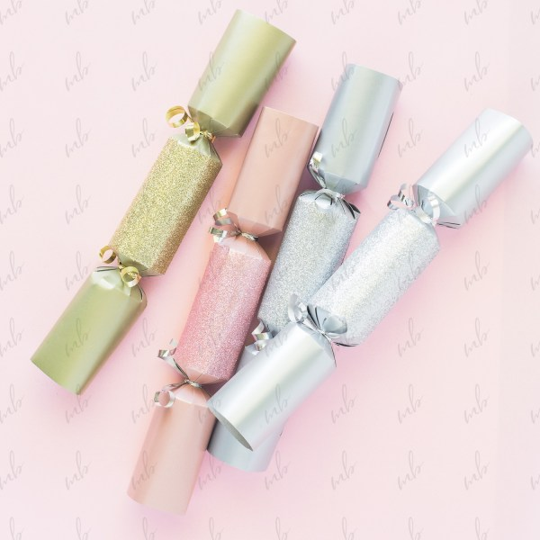 Holiday Styled Stock Photo Christmas cracker bon-bons, pink, gold and silver on a white background