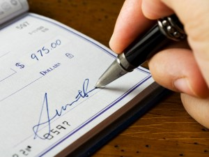 Close up of a hand signing a check.  Please note that the signature is fictitious.