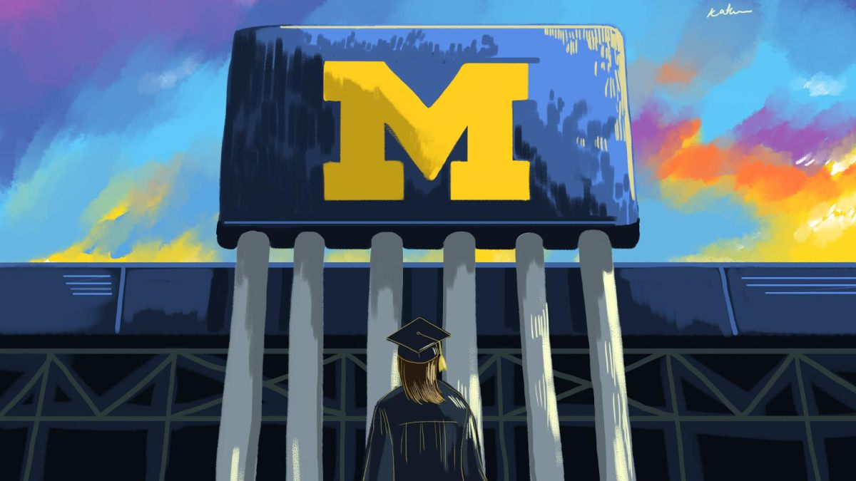 """A female student standing under the Big House """"M"""" with a cap and gown on."""