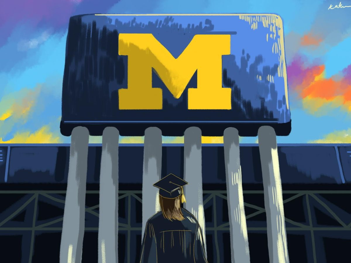 "A female student standing under the Big House ""M"" with a cap and gown on."