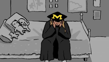 A graduate in a cap and gown sitting on their dorm bed. The scenery is gray.