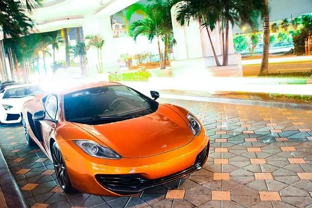 fancy orange car parked on sidewalk