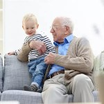 Grandfather and grandson sitting on sofa together at home