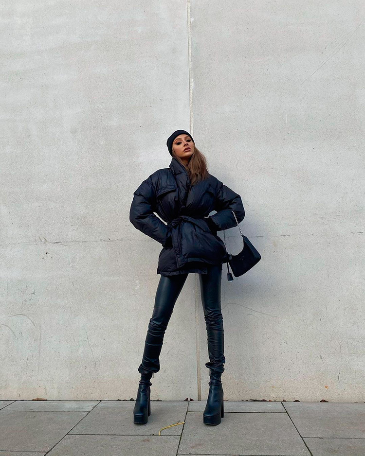A girl in the streets with a total black look from Misspap: puffy jacket, skinny pants and high boots