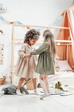 Dos niñas juegan entre ellas, las dos llevan vestido, uno verde y otro rosa, llevan moda infantil de segunda mano